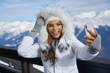 Girl Makes A Selfie In Ski Clothing On Snow Mountain. Stock Photo