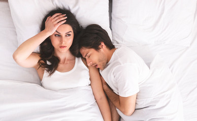 Grumpy woman with insomnia lying with man in bed