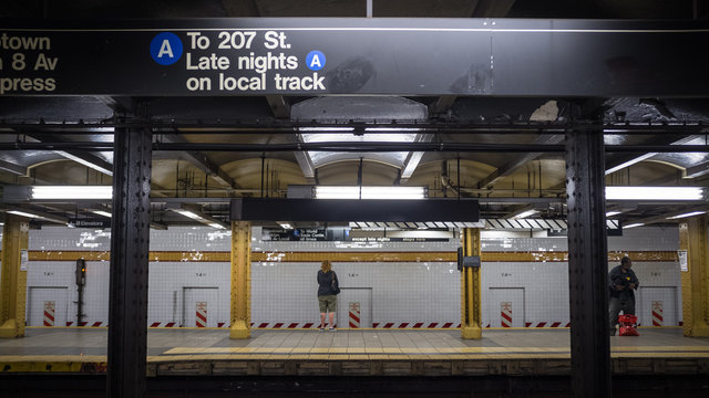 14th Street subway, New York, NYC. A view across the platforms of 14th St. subway station with passengers waiting for the express and local lines.
