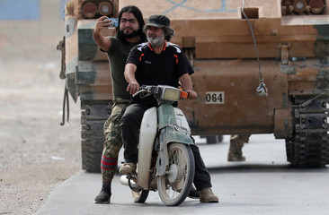 A Turkey-backed Syrian rebel fighter takes a picture with a mobile phone at the border town of Tel Abyad