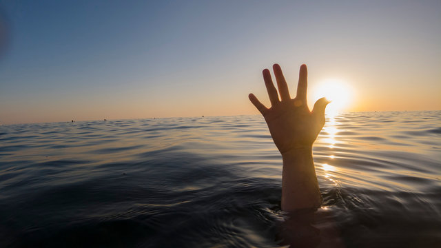 hand of a drowning man in the sea