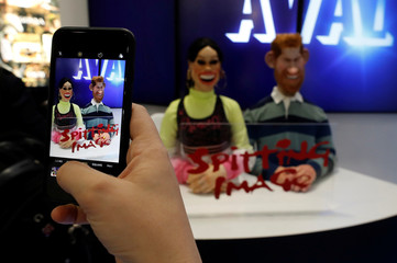 A visitor takes a picture of puppets of Britain's Prince Harry and his wife Meghan, the Duke and Duchess of Sussex, at the stand of British satirical television puppet show Spitting Image during the annual MIPCOM television programme market in Cannes