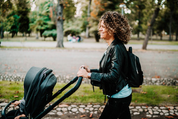 young mother walking her child in city park with a beautiful pram.