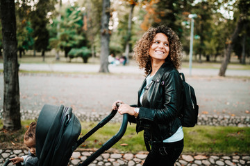 Portrait of happy mom walking pram in park. Curly haired young mother walking baby in park