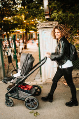 Portrait of happy mom walking baby stroller in park