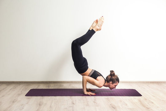 Side view portrait of young adult sporty woman wearing black sportswear standing in scorpion pose, doing vrischikasana exercise, practicing yoga, indoor, studio shot, white background, isolated