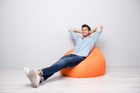 Turned full length body size photo of cheerful confident relaxing man sitting in chair thinking guessing smiling toothily having rest fun isolated over grey color background