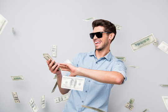 Photo of cheerful excited ecstatic overjoyed man throwing money away showing his wealthiness wearing denim isolated over grey color background