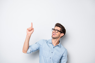 Photo of cheerful positive handsome attractive man pointing up for you to see novelty released recently smiling toothily isolated over grey color background