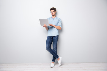 Full length body size photo of focused serious intelligent coworking manager standing confidently with legs crossed searching for news via internet connection isolated grey color background