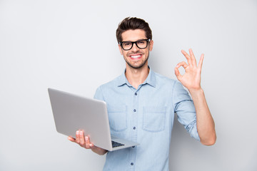 Photo of beaming brown haired cheerful positive kind friendly business trainer having done his teaching project to be shown to his students showing ok sign isolated over grey color background