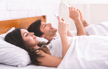 Young couple using cellphones in bed, ignoring each other