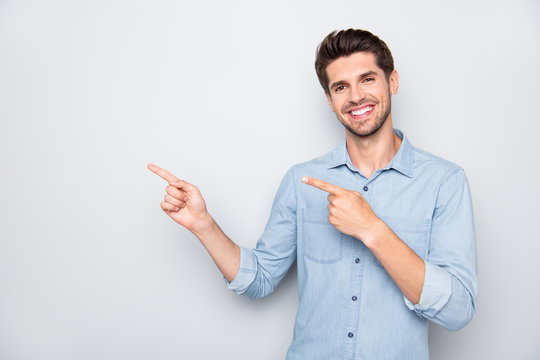 Portrait of positive cheerful man promoter point index finger indicate suggest promo ads wear casual style clothes isolated over grey color background