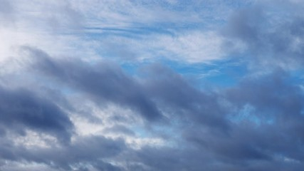 Fotobehang - Dramatic dark stormy clouds moving fast below high clouds in blue sky background. Timelapse, 4K UHD.