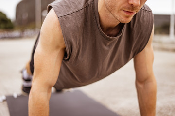 Young athletic man doing workout. Fitness outdoors. Push ups. Urban background.