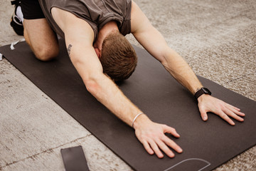 Young athletic man doing workout. Fitness outdoors. Stretching. Urban background.