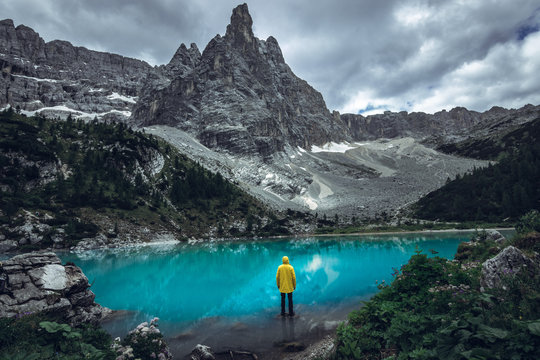 Man in yellow jacket standing alone on the rock at alpine lake Lago di Sorapis in the Italian mountains - Dolomites
