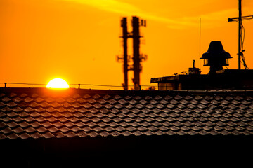 sunrise in in a city with house roof and antenna