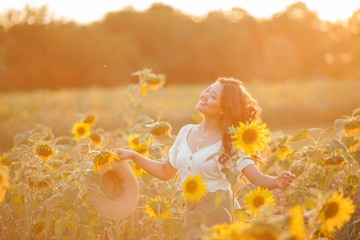 Young Asian woman with curly hair in a field of sunflowers at sunset. Portrait of a young beautiful asian woman in the sun.
