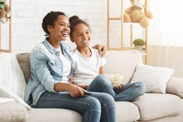 Two cheerful girls enjoying movie, eating popcorn