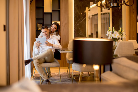 Young couple relaxing at luxurious home with digital tablet