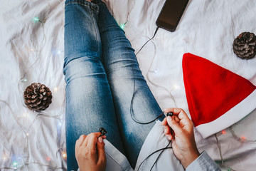 Female listening to music in bed. Pine tree cones, Santa Claus cap and smartphone with earphones near the legs of female. Christmas holidays. X-mas morning. Lazy afternoon.