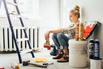 Pretty young woman makes DIY repairs in the house with her own hands. Concept nontraditional gender roles, gender equality, the image of femininity