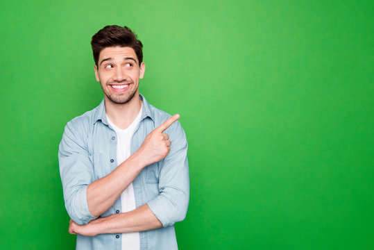 Photo of amazing salesman guy in excited mood indicating finger to empty space advising cool shopping prices wear casual denim shirt isolated green color background
