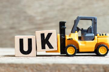 Fototapeta Toy forklift hold letter block k to complete word UK (abbreviation of united kingdom) on wood background obraz