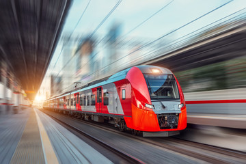 Electric passenger train drives at high speed among urban landscape. Fotomurales