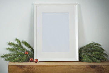 Christmas decorations in bright shiny colors with Christmas lights, picture frames and blurred white wall background.