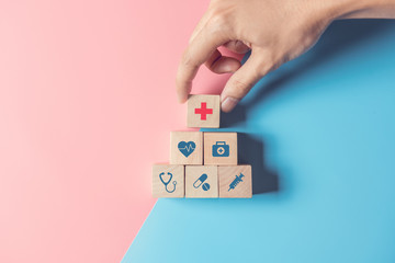 Health Insurance Concept, Hand of man arranging wood cube stacking with icon healthcare medical on pastel blue and pink background, copy space.