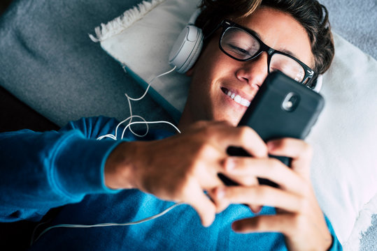 Close up of young phone addicted teenager using mobile cellular lay down on the sofa at home - happy technology millennal people with internet connection device  listening music with heaphones