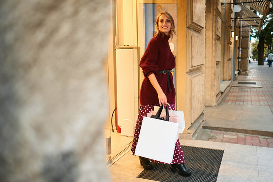 Beautiful stylish blond girl in knitted sweater with bags happily leaving store after shopping