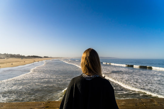 Beautiful girl looking over the pacific ocean in California