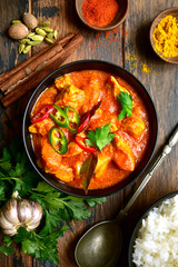 Chicken tikka masala - traditional dish of indian cuisine in a clay bowl .