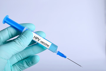 Vaccination healthcare concept. Hands of doctor or nurse in medical gloves with medical syringe ready for injection  a shot HPV vaccine. close up, selective focus - Image