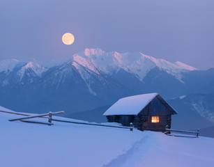 Christmas landscape with a snowy house in the mountains on a moonlit night