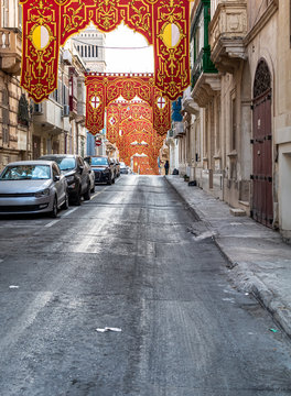 Street in Sliema, Malta, decorated with red religious ornate banners for village feast (festa) of St Gregory the Great.