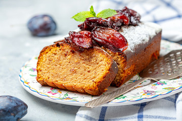 Sliced plum cake with almonds and spiced plum.