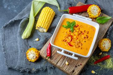 Creamy corn soup with chili in a white bowl.