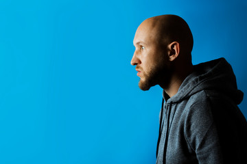 Man with a serious face in profile dressed in a hoodie on a blue background