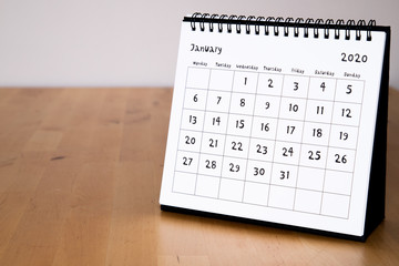 Month page: January in 2020 paper calendar with funny font on the wooden table