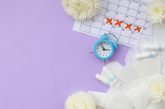 Menstrual pads and tampons on menstruation period calendar with blue alarm clock and white flowers