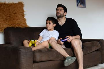 Padre latino juega con su hijo en sofá