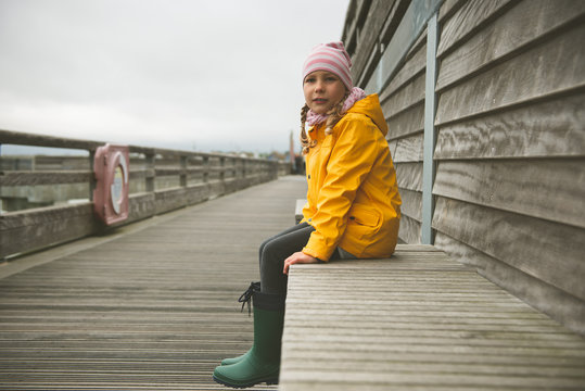 Portrait of little girl in yellow jacket on wooden pier at rainy weather