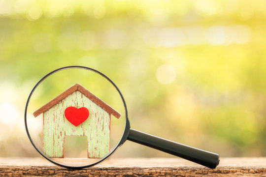 Magnifying glass with home model with red heart put on the wood on bokeh background, Loan for real estate and searching for buy a new house to family in the future concept.