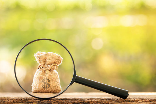 Magnifying glass with searching for money bag put on the wood on bokeh background, Loan and find for business investment fund  in the future concept.