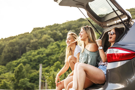 Group of female best friends on travel . They sitting on car trunk and relaxing after long journey.