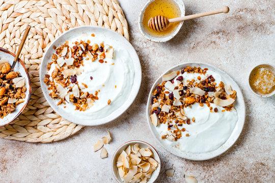 Breakfast bowls with granola, yogurt, coconut chips and honey. Healthy vegan, vegetarian breakfast table